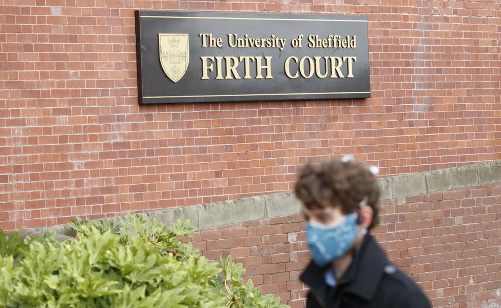 Man in facemask walks past University of Sheffield sign