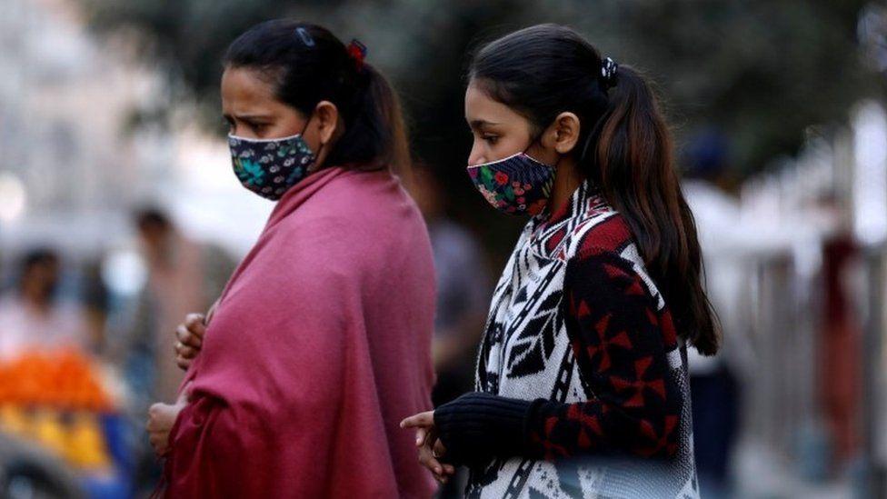 Women with masks against COVID-19 walk outside a market in Karachi, Pakistan January 25, 2021