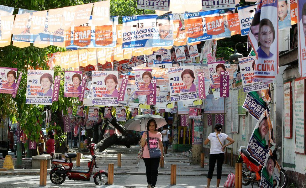 A woman under an umbrella walks under election posters hanging across the street in Tondo, Manila, 5 May
