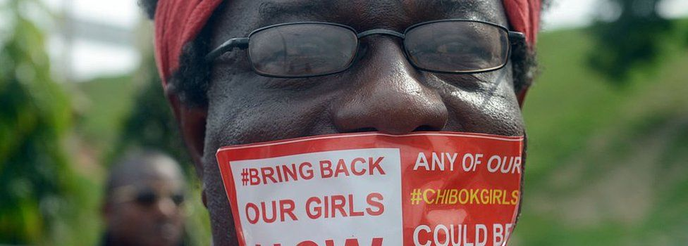 A man seals mouth with a branded sticker reading 'Bring Back Our Girls Now'