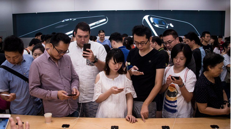 Customers trying out an iPhone 7 in a shop in China