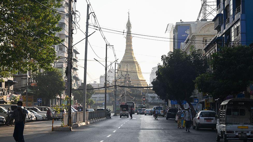 Orang-orang berjalan di sebelah Pagoda Sule di jalan kosong di pusat Yangon pada 1 Februari 2021