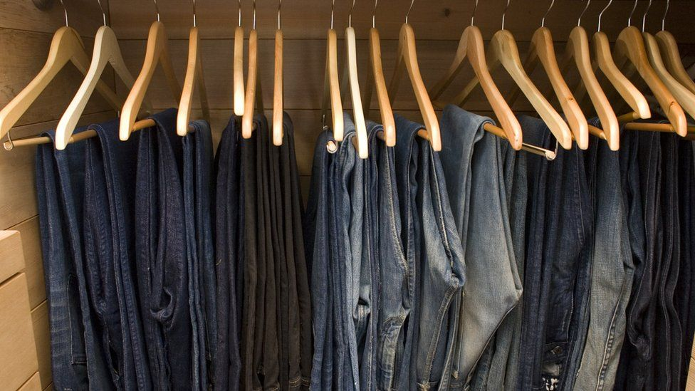 Rows of jeans in a wardrobe