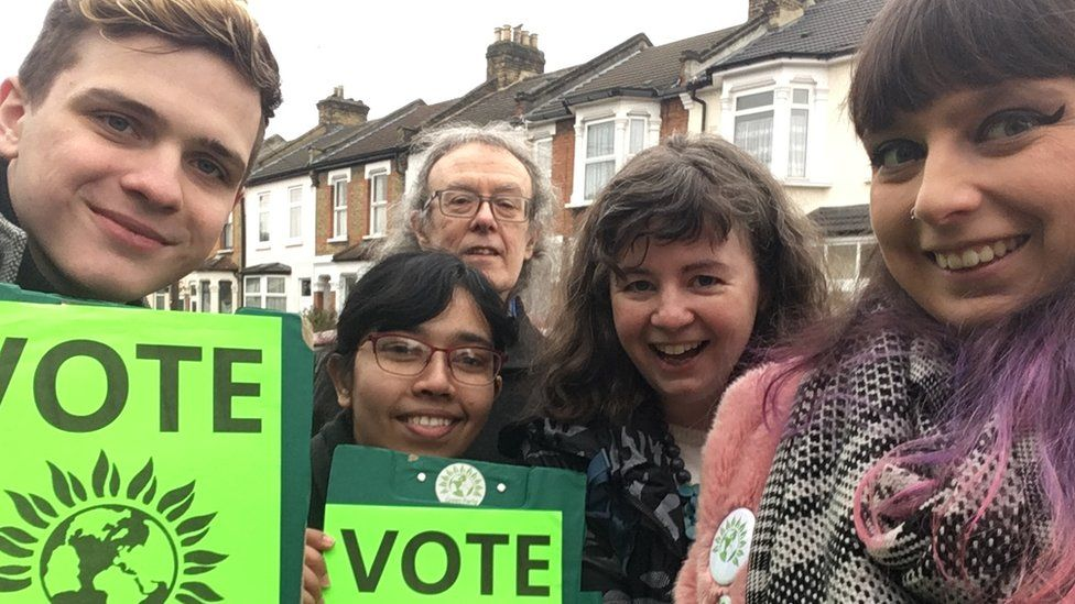 Frankie-Rose Taylor, right, and a group of campaigners holding 'vote Green' placards