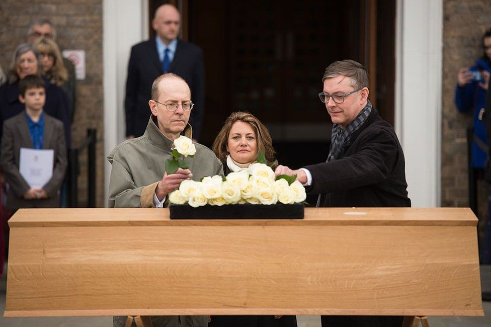Michael Ibsen and two other descendants place roses on the oak coffin with the remains of the monarch during a service held outside the University of Leicester in Leicester, Leicestershire, England on March 22, 2015, prior to a ceremonial procession towards the new site of the king's reinterment some 530 years on from his violent death in 1485 at the Battle of Bosworth.