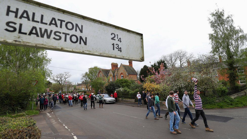 """Villagers from Medbourne in Leicestershire parade a """"bottle"""" through the village before their annual bottle kicking match with neighbouring Hallaton"""