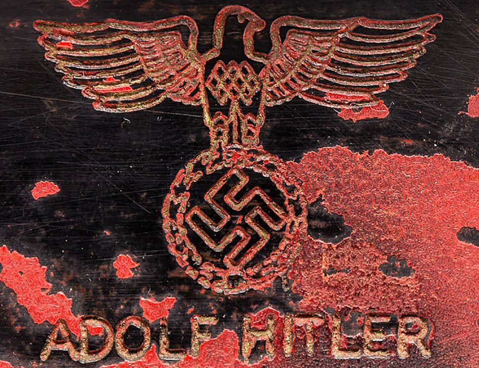 The inscription on the telephone, saying Adolf Hitler, with a Nazi symbol