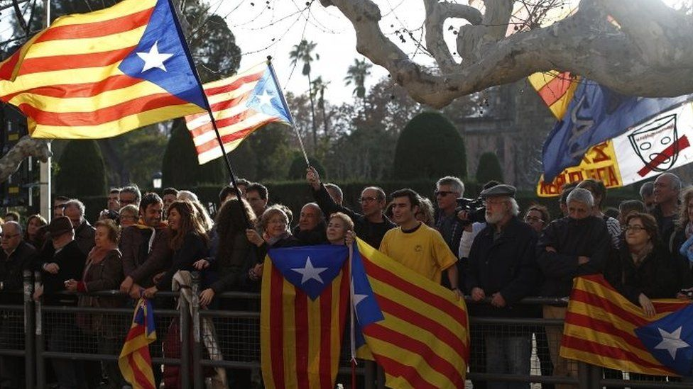 """People wave """"estelada"""" or pro-independence flags prior to the investiture session at the Catalonian parliament in Barcelona"""