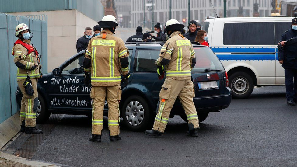 Firefighters work near a car which crashed into the gate of the main entrance of the chancellery in Berlin