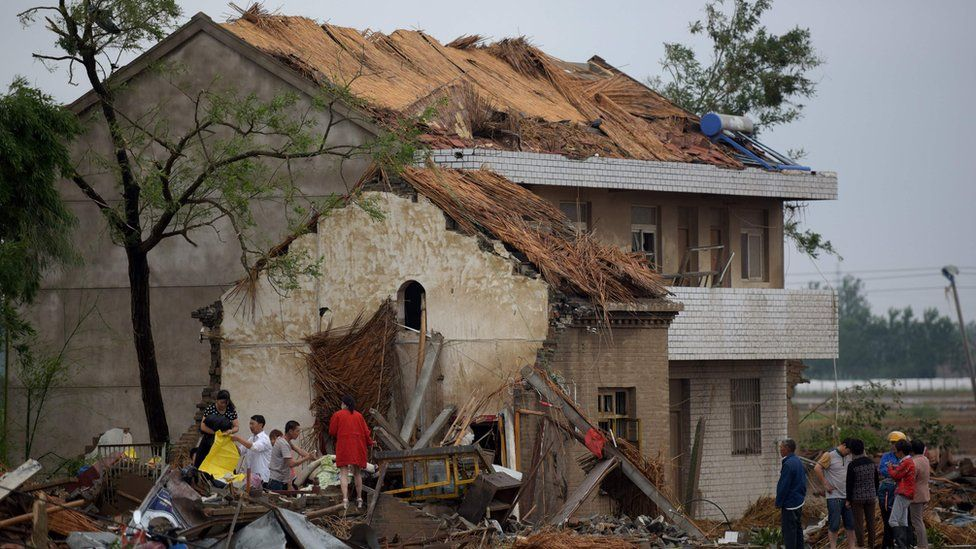 """Residents walk in the rubble of destroyed houses after a tornado in Funing, in Yancheng, in China""""s Jiangsu province on June 24, 2016."""