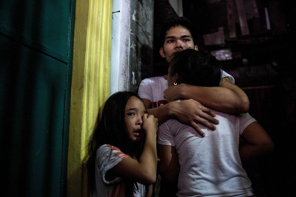 This picture taken on 5 January 2017, shows relatives crying as coroners carry away the body of an alleged drug dealer killed during a drug buy bust operation in Manila