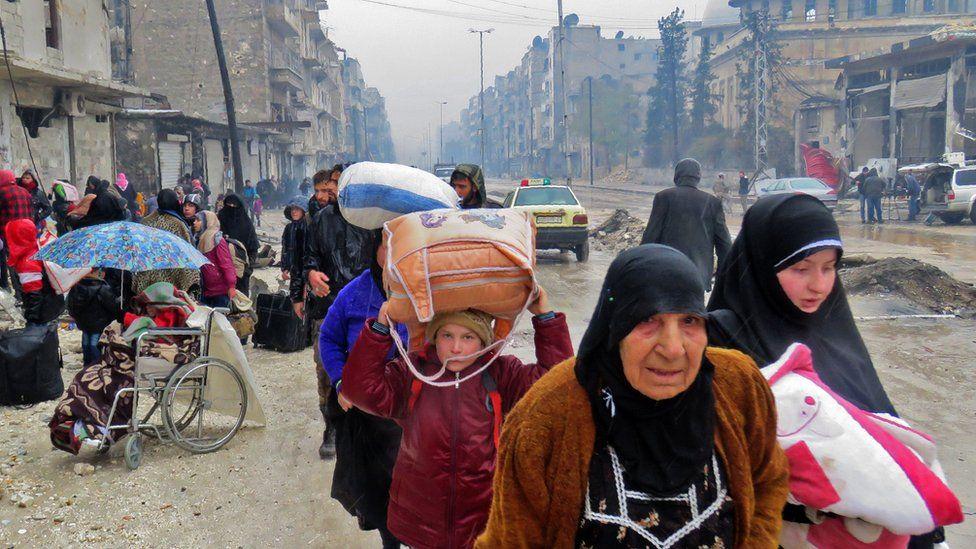 Syrian civilians flee the Bustan al-Qasr district of Aleppo during fighting on 13 December 2016