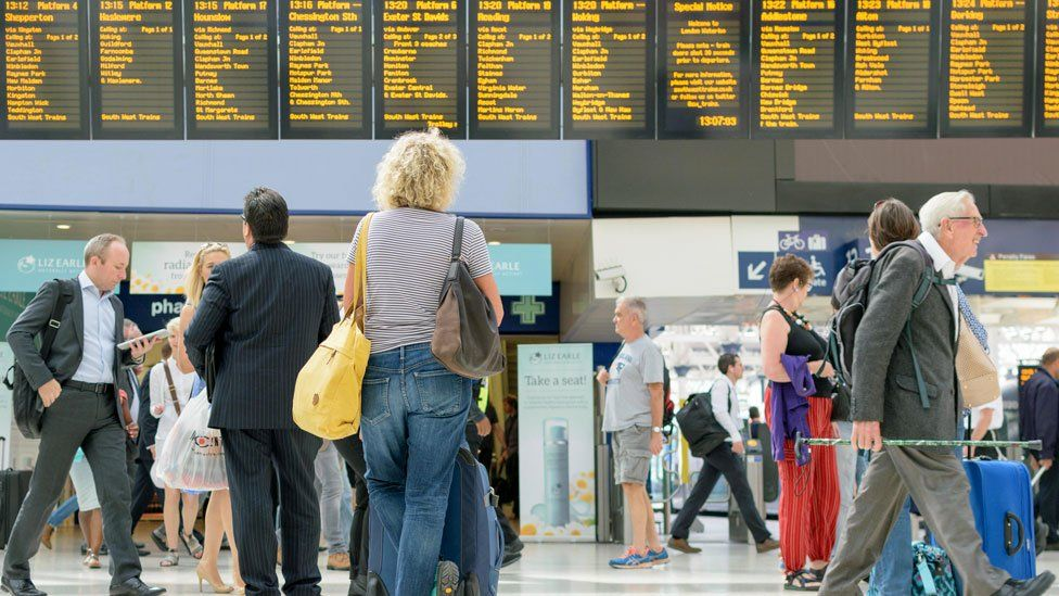 Commuters in a train station looking at the arrivals board