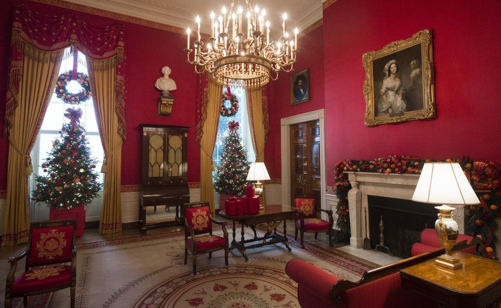 Christmas trees and holiday decorations in the theme of, 'The Gift of the Holidays,' are seen in the Red Room of the White House in Washington, DC, November 29, 2016