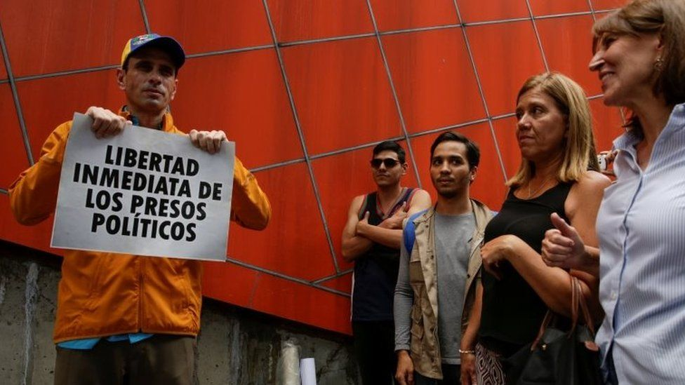 """Venezuelan opposition leader and Governor of Miranda state Henrique Capriles (L) poses for a photo with a placard that reads """"Immediate release of political prisoners"""" in Caracas, Venezuela July 3, 2017."""