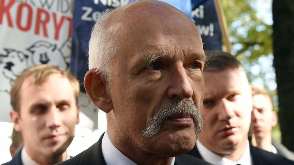 Polish right-wing politician and European Parliament member Janusz Korwin-Mikke talks to reporters in front of the Polish parliament building in Warsaw