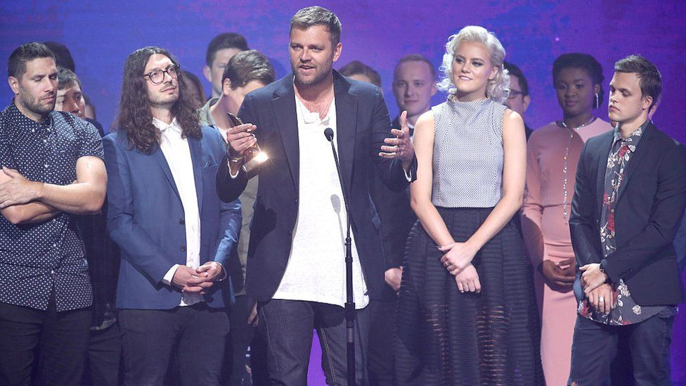 Joel Houston of Hillsong United accepts an award onstage during the 2016 Dove Awards in Nashville, a Christian music awards show