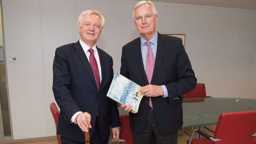 David Davis and Michel Barnier holding each other's gifts