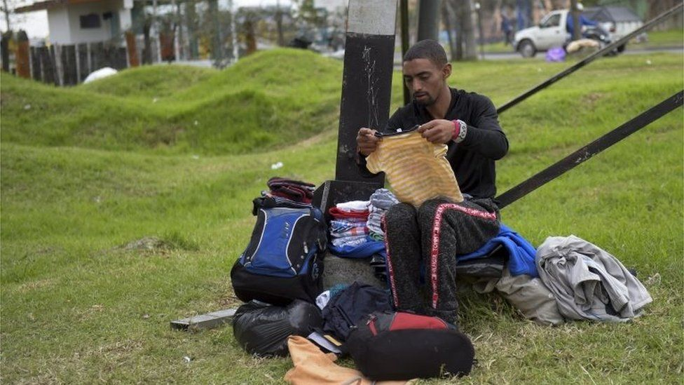 A Venezuelan migrant sorts out donated clothes at an improvised camp near a bus terminal in Bogota on September 11, 2018