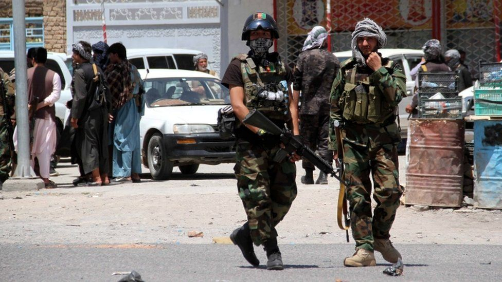 Afghan security officials patrol after they took back control of parts of Herat city