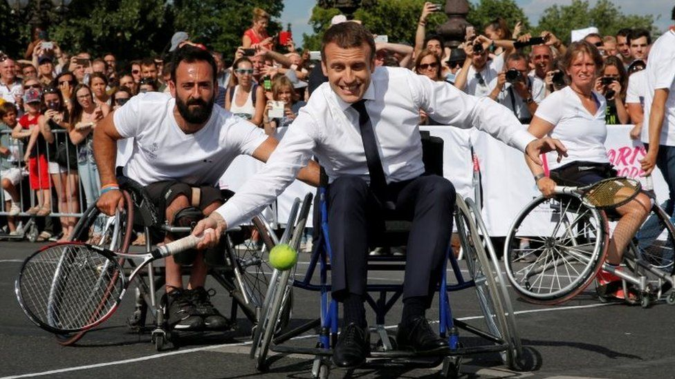 French President Emmanuel Macron returns the ball while sitting in a wheelchair as he plays tennis on the Pont Alexandre III in Paris, France, on 24 June 2017.