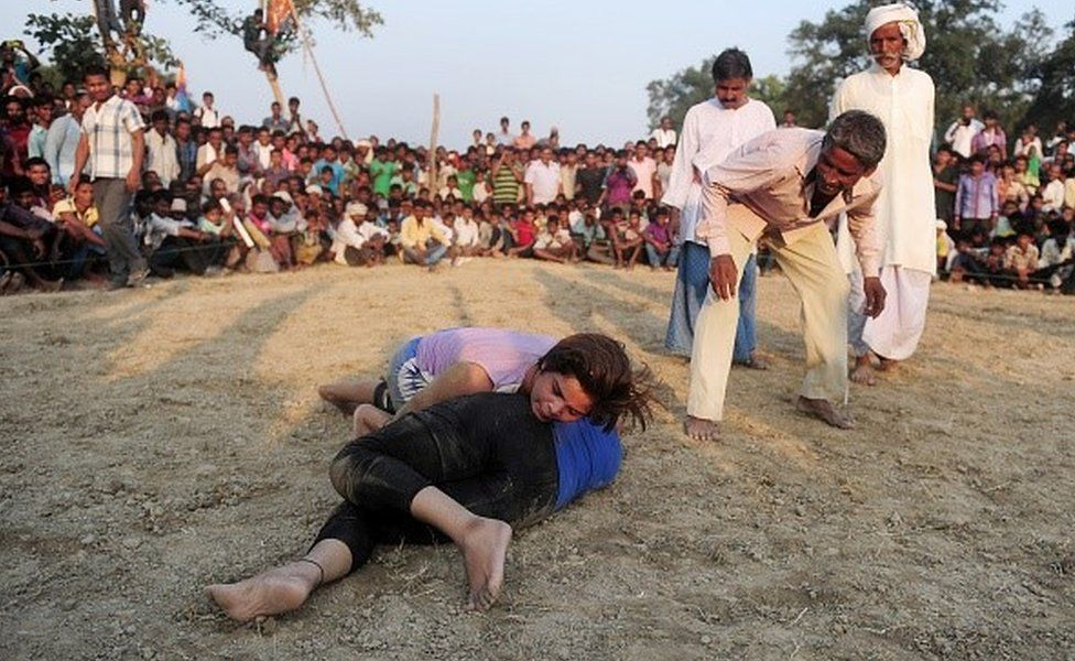Indian women wrestlers perform during a traditional wrestling competition at a fair held annually on October 7 in Rampur village, near Allahabad on October 7, 2015.