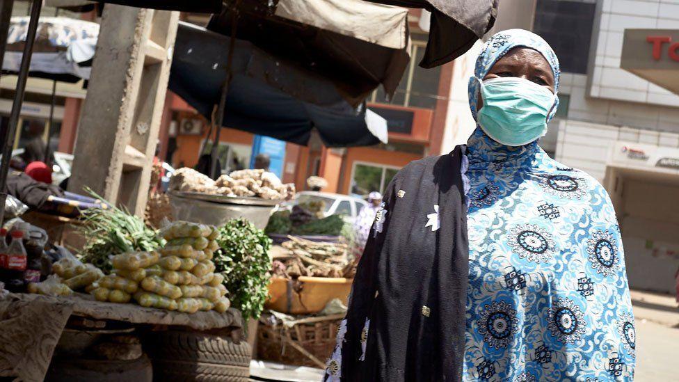 A market seller wearing a mask