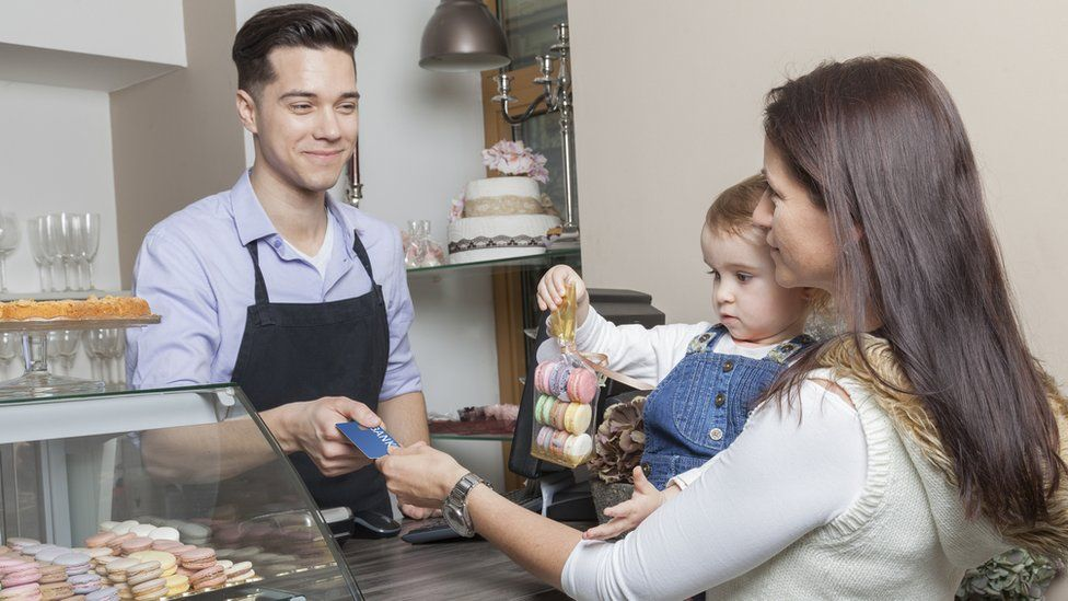 Woman with baby paying in a cake shop