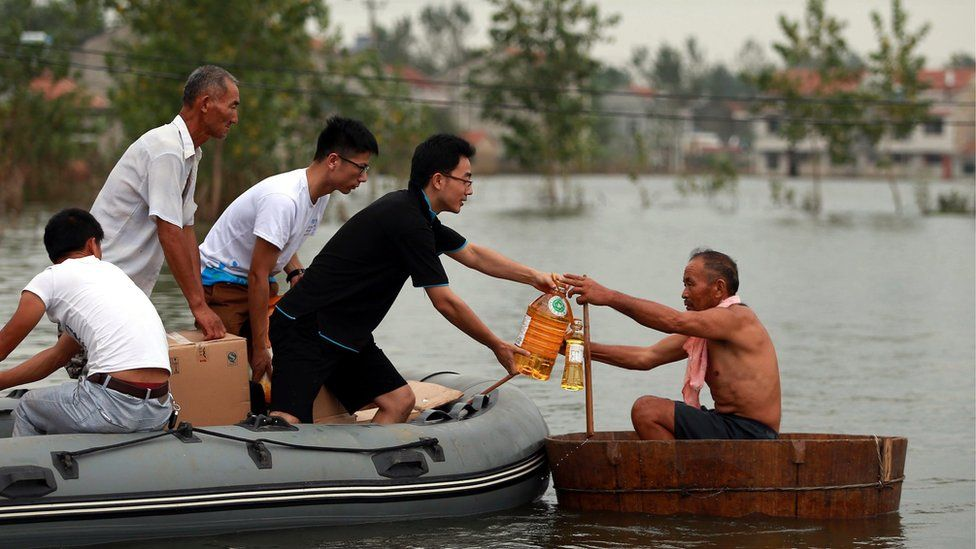 A picture made available on 23 July 2016 of volunteers giving food supplies to a villager in a makeshift boat on flood water, Xinhua Village of Xinchang county in Wuhan city, Hubei Province of central China on 18 July 2016.