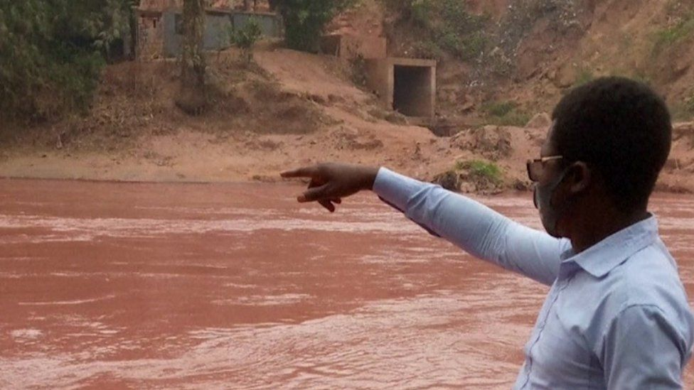 Man pointing at red river