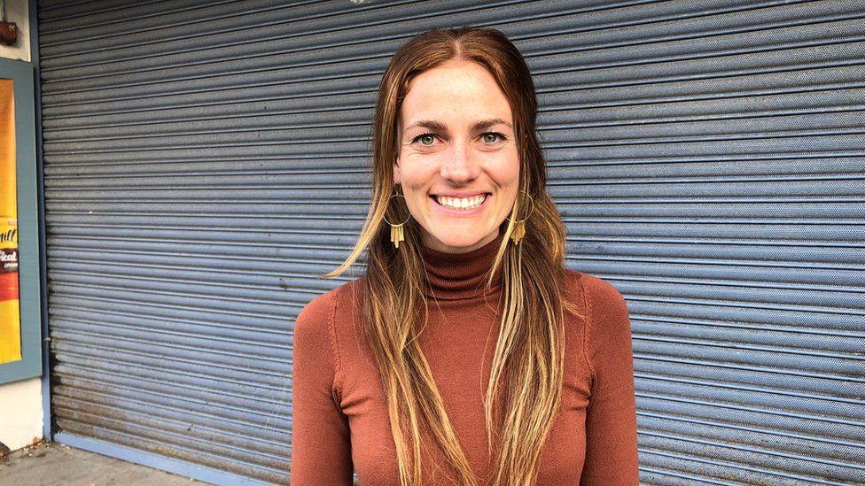 Yoga teacher Kellie Walker in front of shop shutters