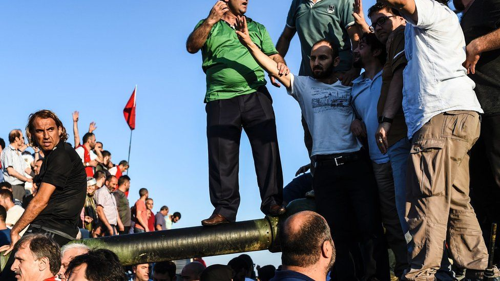People stand and celebrate on an army tank after taking over military position on a major Bosphorus bridge in Istanbul (16/07/2016)