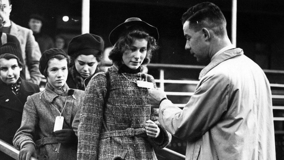 Young woman's identify tag is checked as she leaves a boat at Harwich, Essex, on 2 December 1938