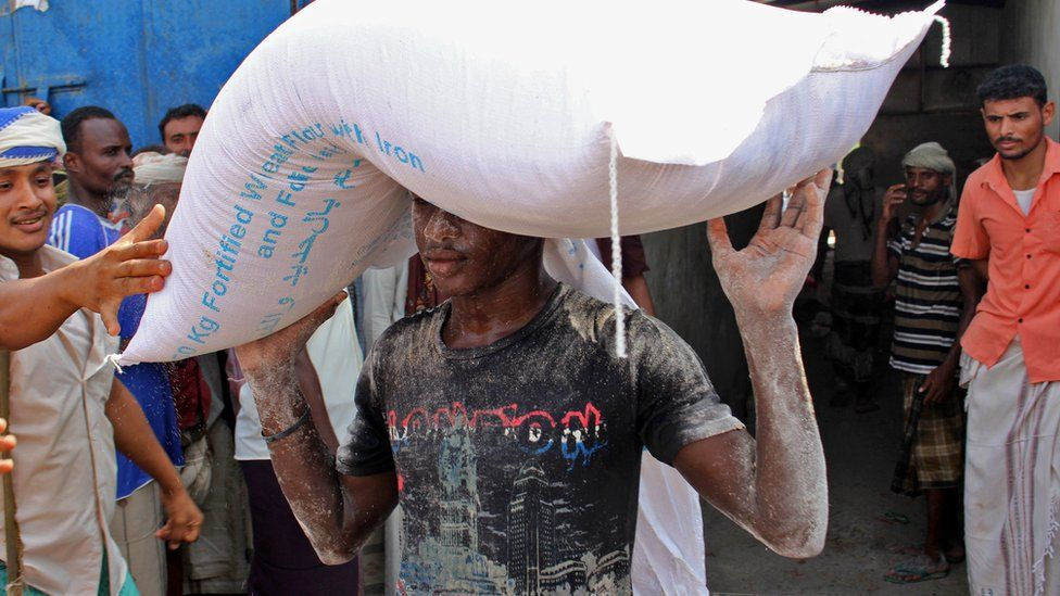 An aid workers carries a sack of flour distributed by the World Food Programme