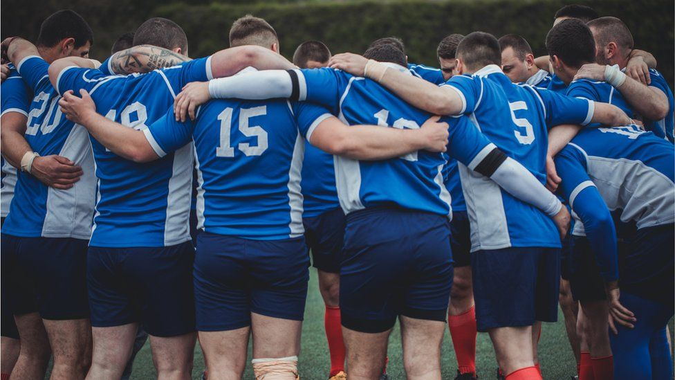Young rugby team in a group huddle