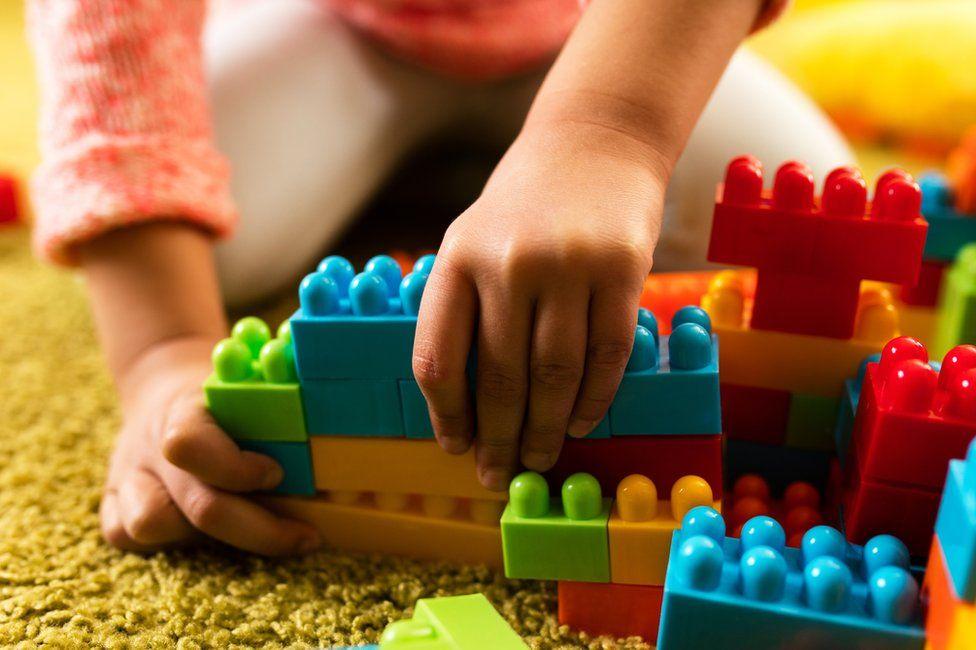 A child plays with plastic bricks