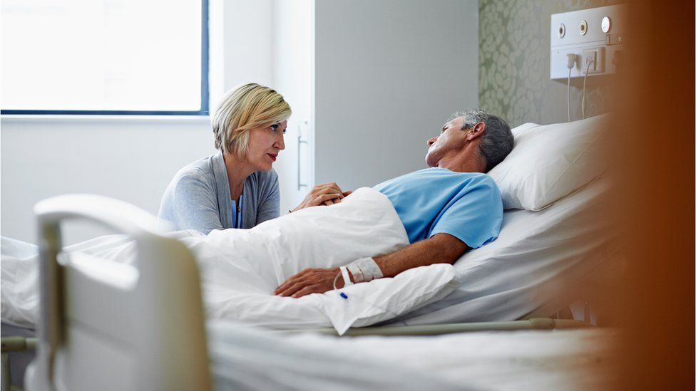 Woman holding man's hand in hospital
