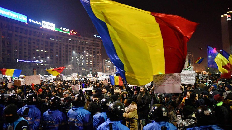 Riot police stand guard as people demonstrate in front of government headquarters in Bucharest, on February 1, 2017