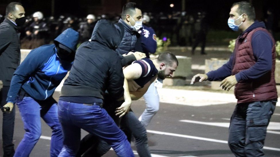 A group of protesters appear to scuffle in the street