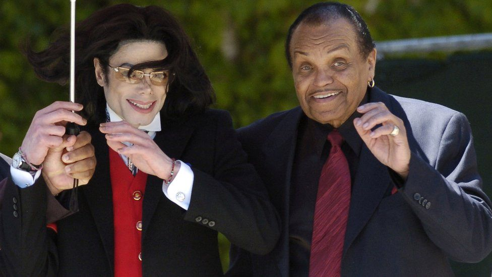 Pop star Michael Jackson and his father Joe Jackson gestures to his fans