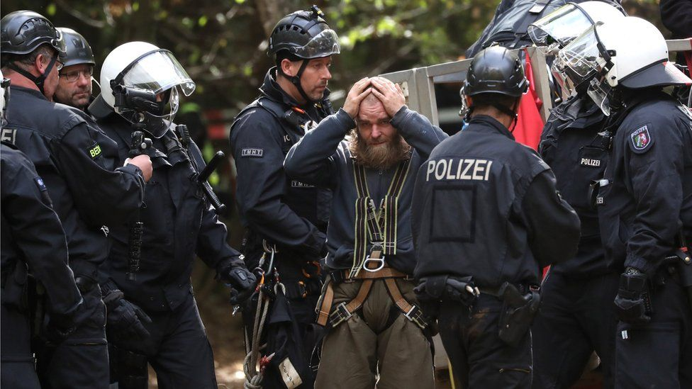 An activist is escorted by police