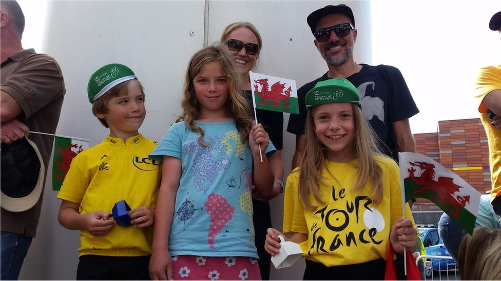 Family of two parents and three children wearing yellow and holding Wales flags