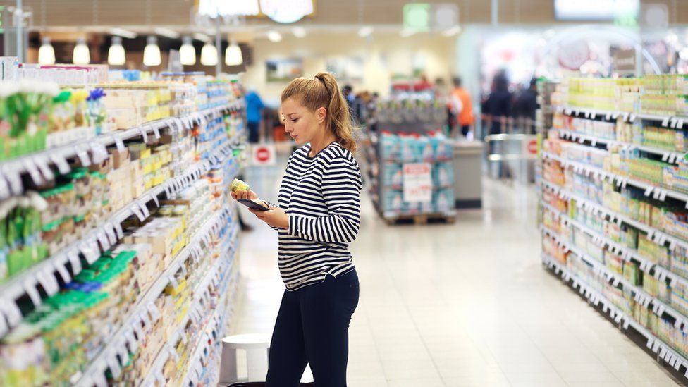 Woman looking at baby food ingredients in a supermarket