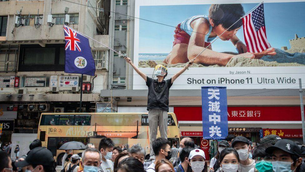 A protestor waving the US and Hong Kong colonial-era flags