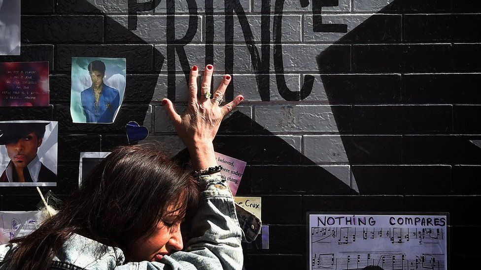 Prince fan touches the star of music legend Prince who died suddenly at the age of 57