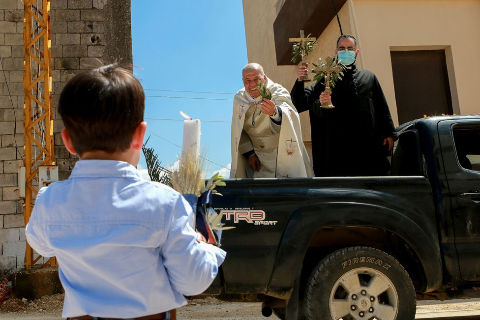 A priest stands on the back of a truck as he visits neighbourhoods in Qlayaa, Lebanon, on 28 March 2021