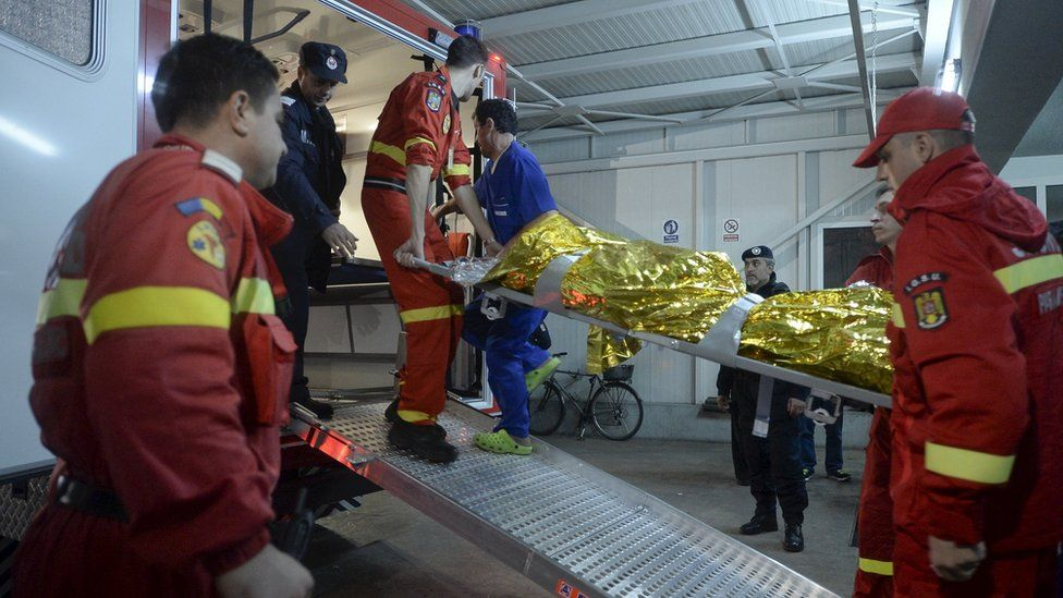 Paramedics carry an injured person at a hospital in Bucharest, Romania