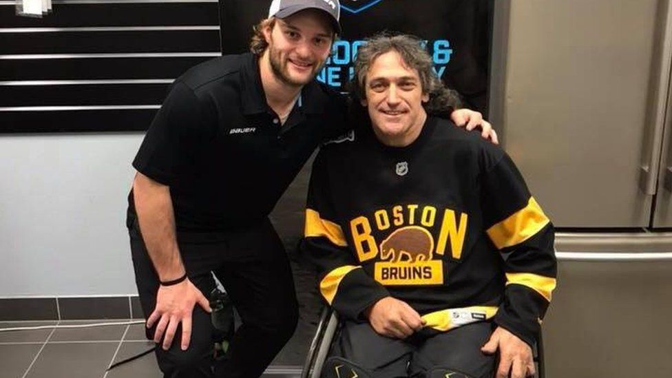 Darren Belling pictured in a wheelchair, next to a friend