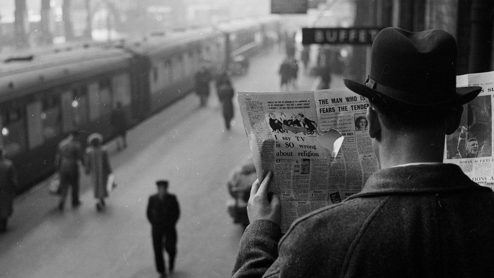 A secret agent at a train station looks through a hole in a newspaper