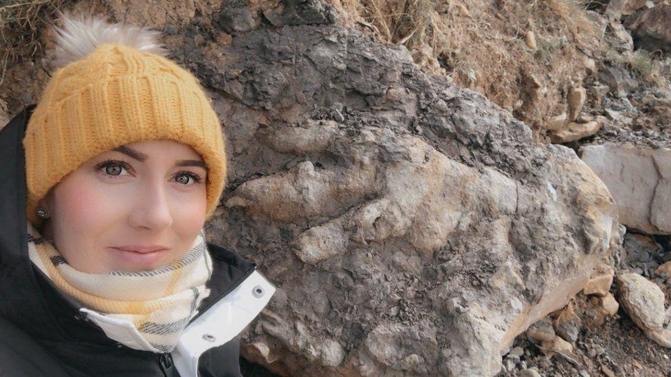 Archaeologist Marie Woods with a dinosaur footprint